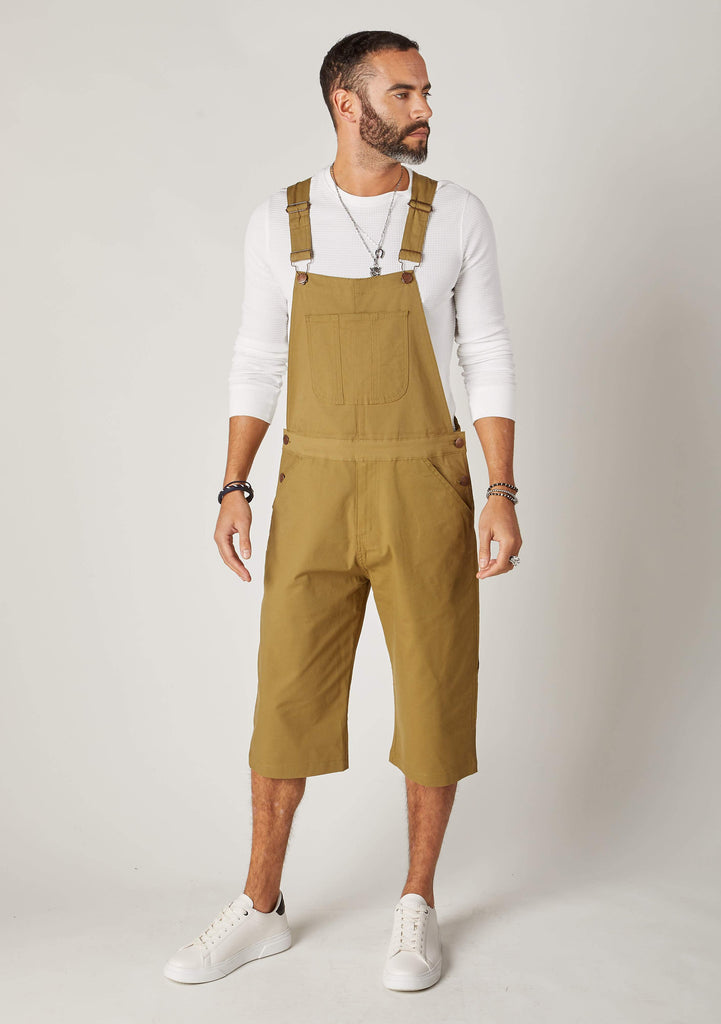 Full frontal pose angled to his left wearing olive coloured dungaree shorts from Dungarees Online.