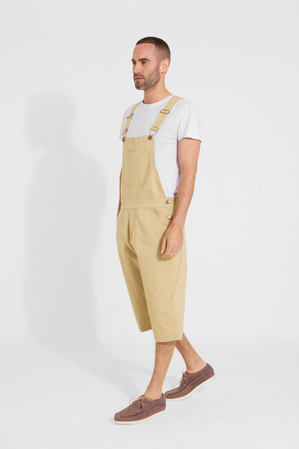 Full frontal pose angled to his right and walking, wearing bib-up sand coloured dungaree shorts from Dungarees Online.