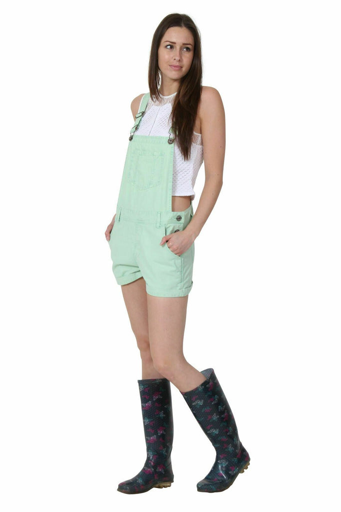 Angled front-side pose with hands in front pockets wearing pale green, relaxed-fit bib-overall shorts from Dungarees Online.