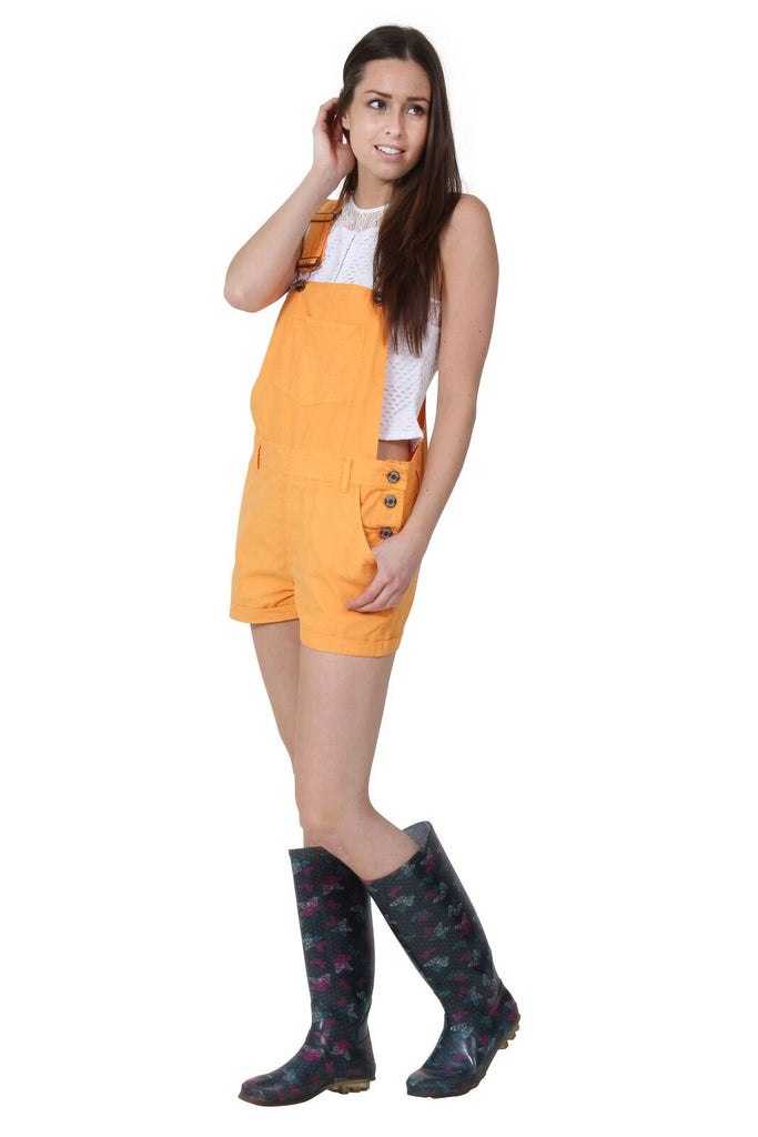 Angled front-side pose with hand in left-front pockets wearing pale orange, relaxed-fit bib-overall shorts from Dungarees Online, with clear view of one-side button fastening.