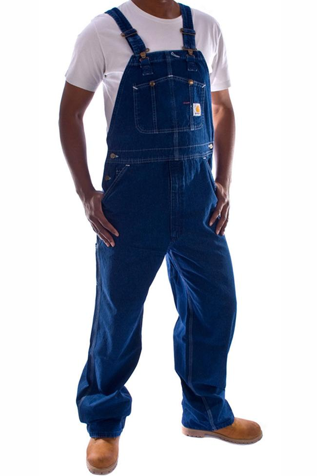 Angled frontal pose facing slightly left with thumbs in reinforced pockets, wearing Carhartt R07 stonewash denim dungarees.
