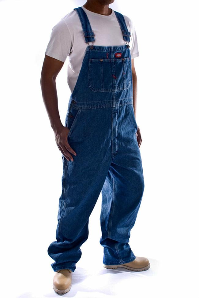 Angled frontal pose with thumbs in side pockets wearing Dickies stonewash denim overalls from Dungarees Online.