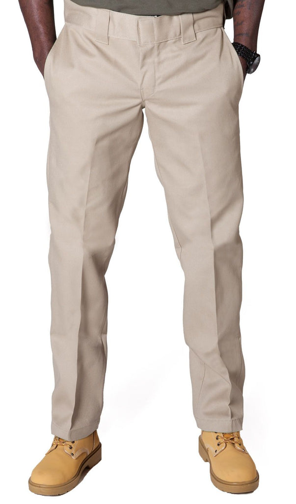 Closer front view of Dickies slim fit 873 work pant in khaki with hands in front pockets, showing permanent crease, twill fabric and tunnel belt loops.