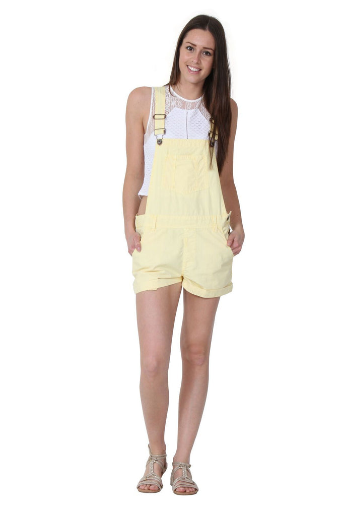 Full frontal of ladies' pale yellow, bib-overall shorts with adjustable straps and hands in front pockets, paired with white t-shirt and sandals.