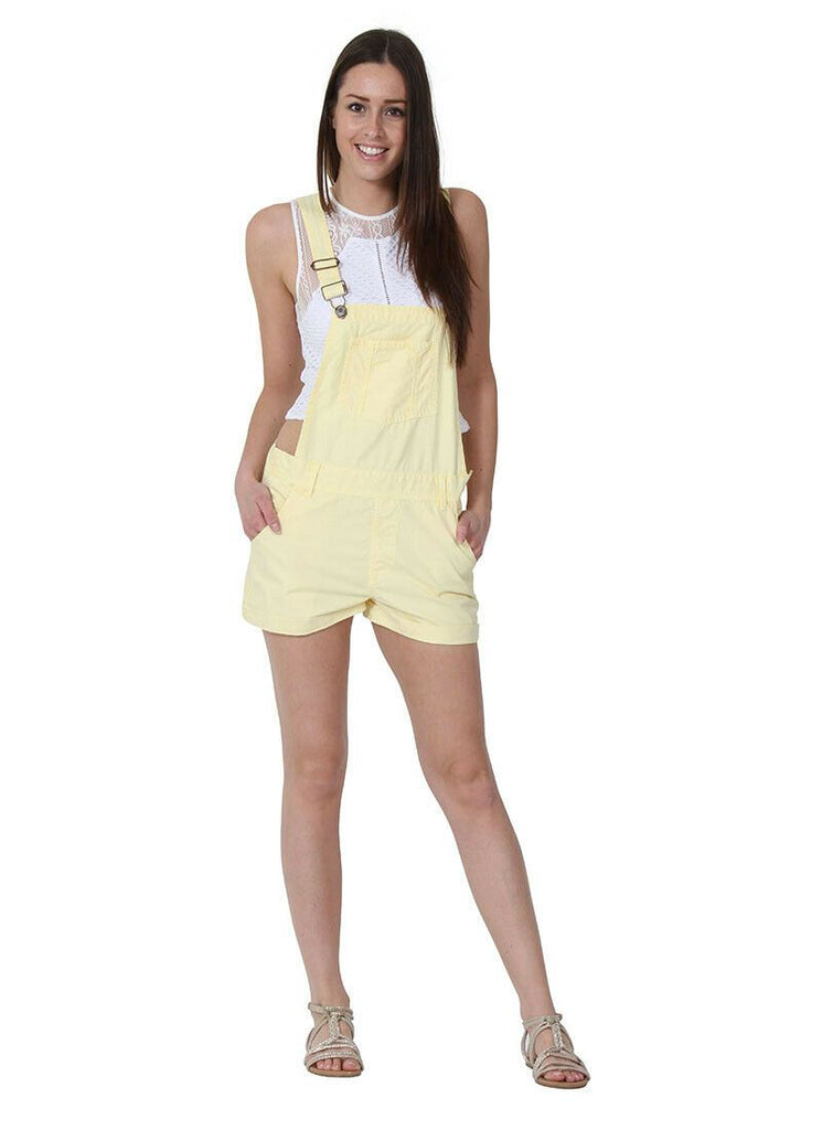 Leaning on right hip, wearing ladies' pale yellow, bib-overall shorts with adjustable straps and hands in front pockets, paired with white t-shirt and sandals.