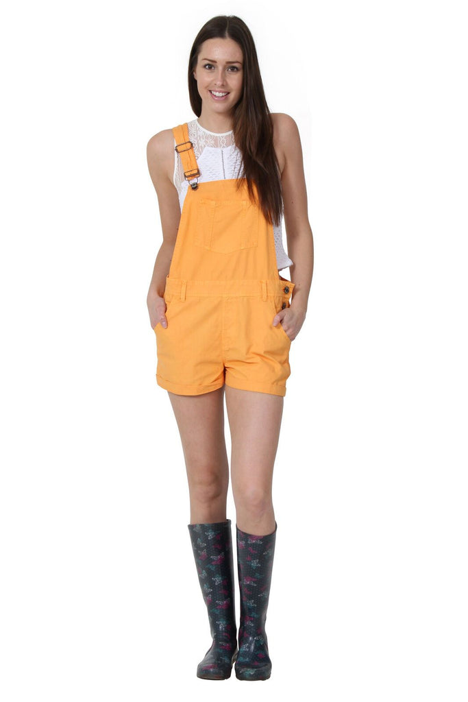 Full frontal of ladies' orange, bib-overall shorts with adjustable straps and hands in front pockets, paired with white t-shirt and wellies.