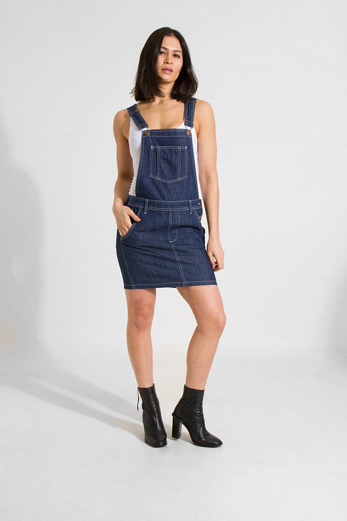 Slightly distant, full frontal pose looking straight ahead with right hand in pocket, wearing indigo denim dungaree dress from Dungarees Online.