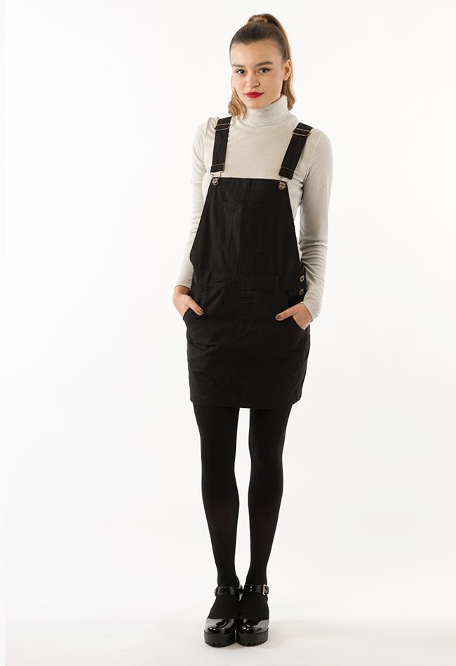 Full frontal pose looking straight ahead with hands in pockets, wearing black overall dress from Dungarees Online.