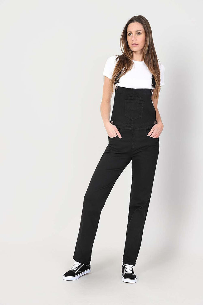 Hands in front pockets and leaning on left hip, wearing ladies' black, regular fit dungarees.