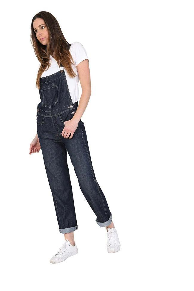 Walking in ladies' dark-wash, regular fit dungarees with view of side button fastening, paired with white t-shirt and trainers.