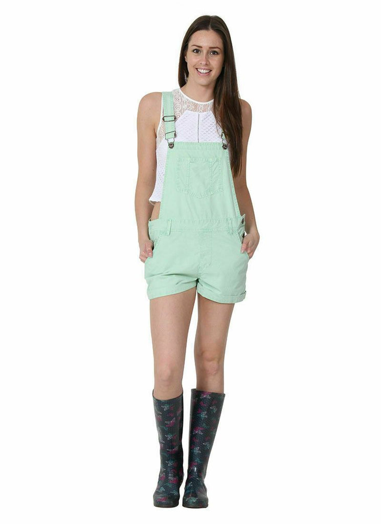 Full frontal view of ladies' bib-overall shorts with adjustable straps and hands in front pockets, paired with white t-shirt and wellies.