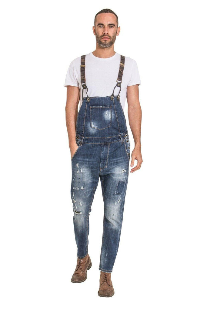 Walking pose with full-front view of men's 'Lazlo' distressed denim bib-overalls with hand in front-right pocket.