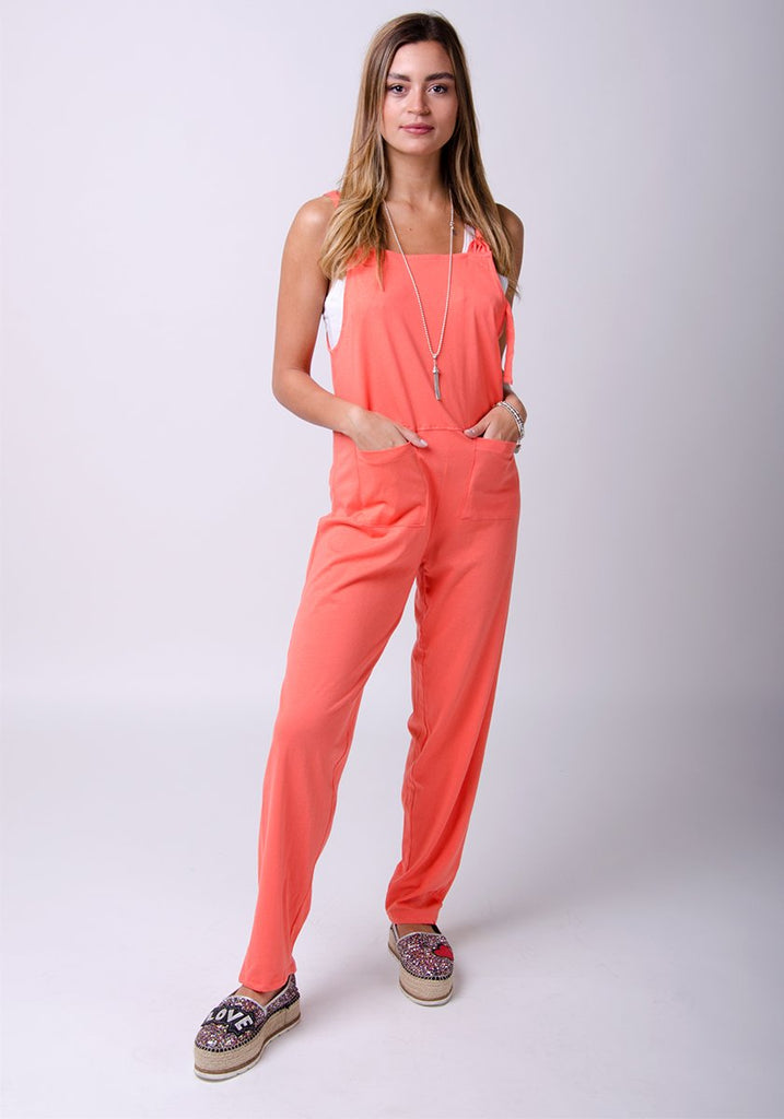 Full frontal pose with hands in front pockets, wearing practical coral jersey jumpsuit.