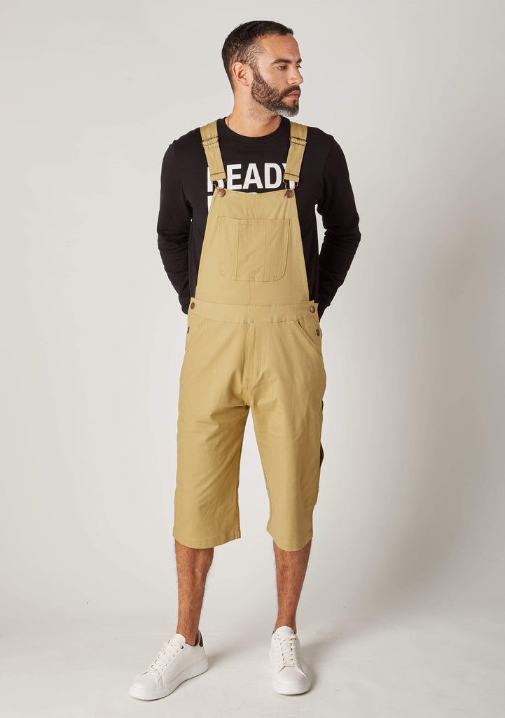 Pose looking to left with hands behind back, wearing loose fitting khaki cotton dungaree shorts.