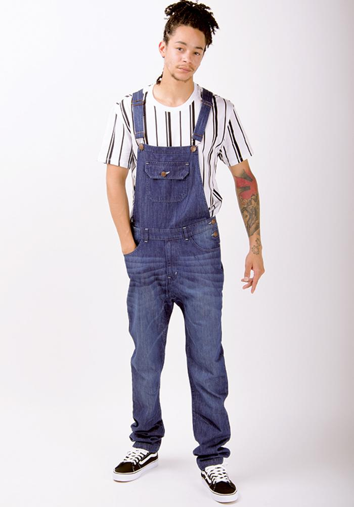Full front pose wearing slim-fit, organic bib-overalls with hand in right pocket.