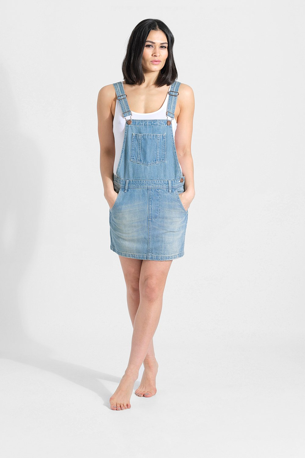 Slightly distant, full frontal pose looking straight ahead with hands in pockets and legs crossed, wearing denim overall dress from Dungarees Online.