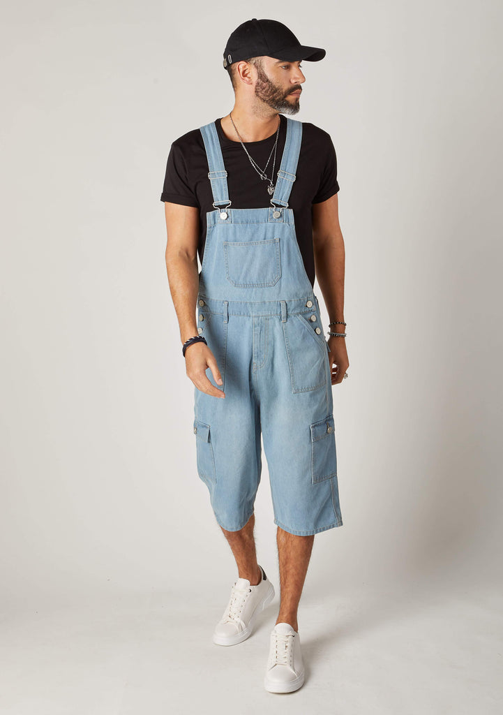 Full frontal walking pose looking to left wearing dungarees shorts for men with adjustable straps up.