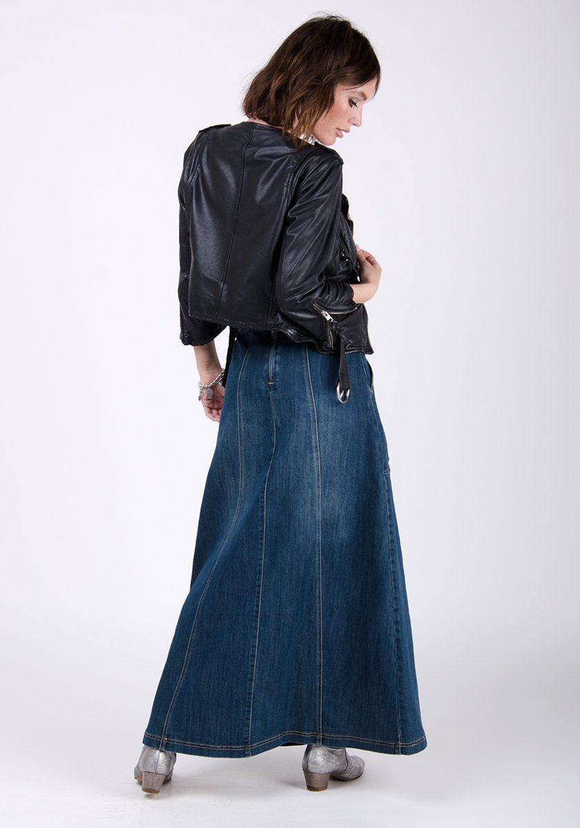 Full-rear pose looking to her right wearing full flared shape of maxi skirt paired with dark leather jacket.