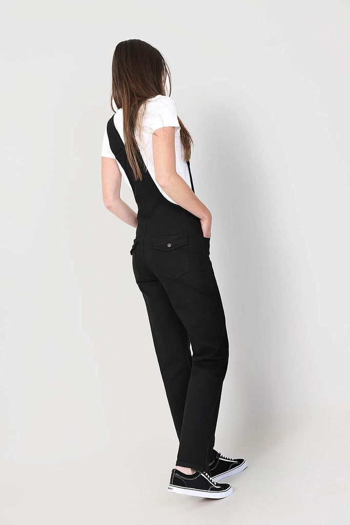 Angled rear-side pose with hands in front pockets wearing black, regular fit bib-overalls from Dungarees Online.