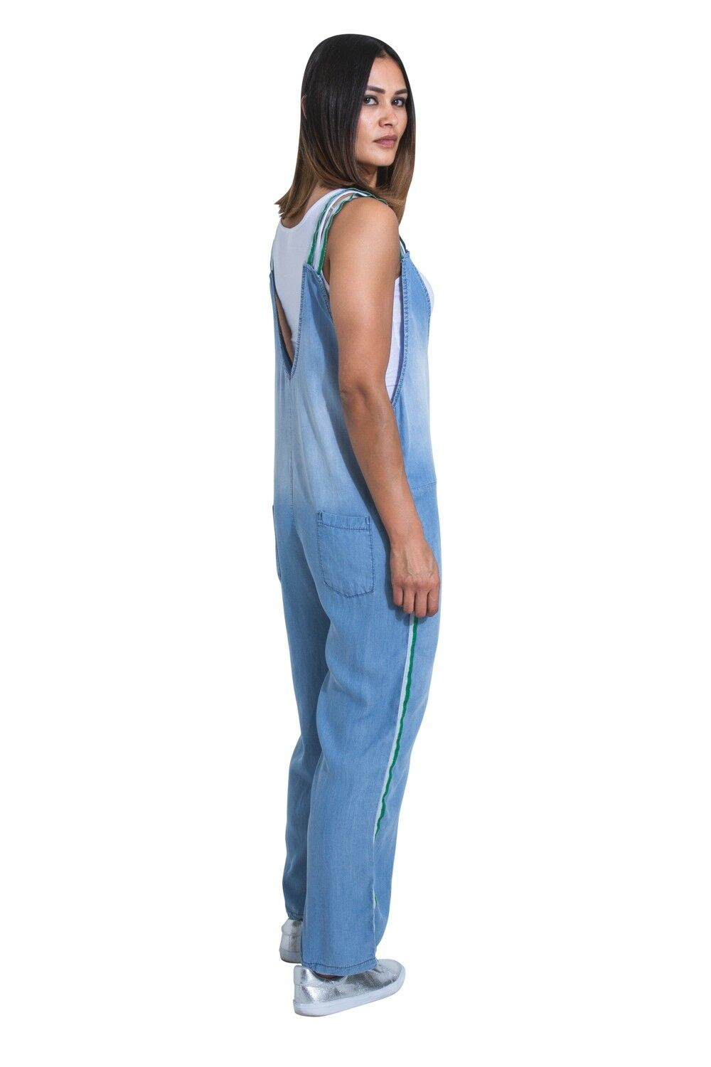 Standing upright with side view of all-in-one light-blue playsuit, showing rear pockets and green stripe down the leg seam.