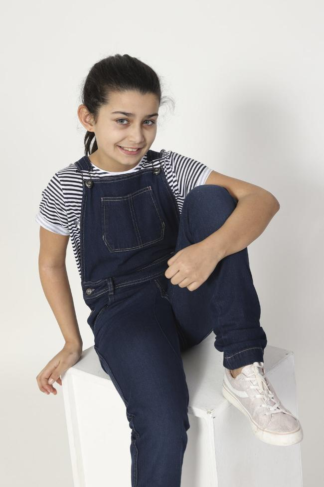 Girl sitting on box, wearing durable machine washable, Libby style kids overalls from Dungarees Online.