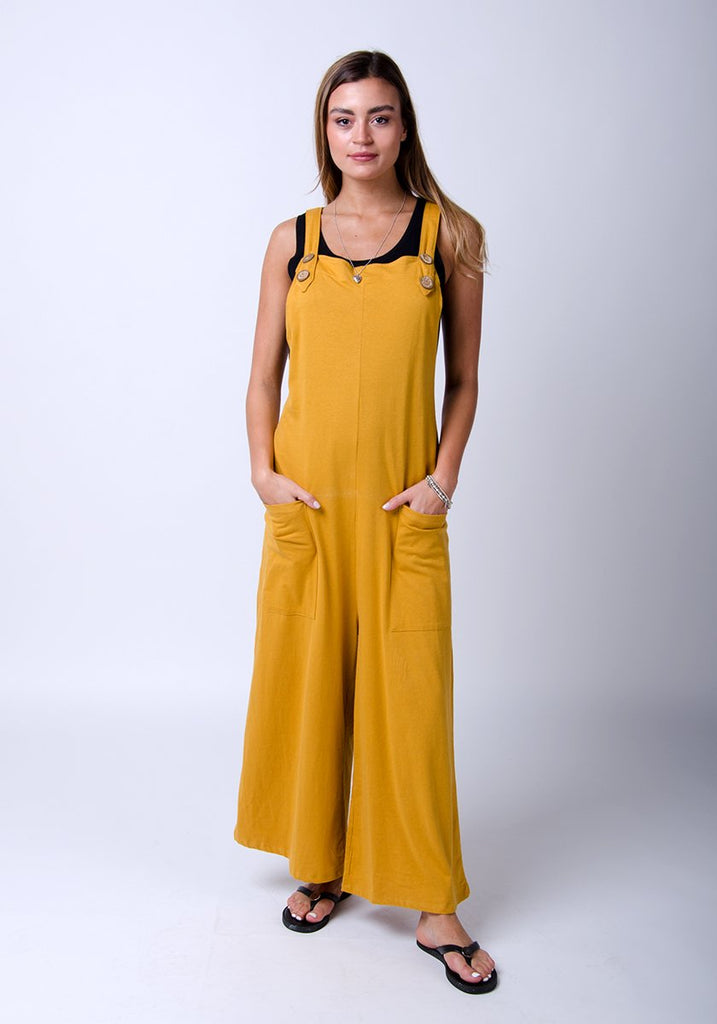 Frontal, full-length model with hands in pockets wearing our gold, cotton jersey, wide-leg dungaree.
