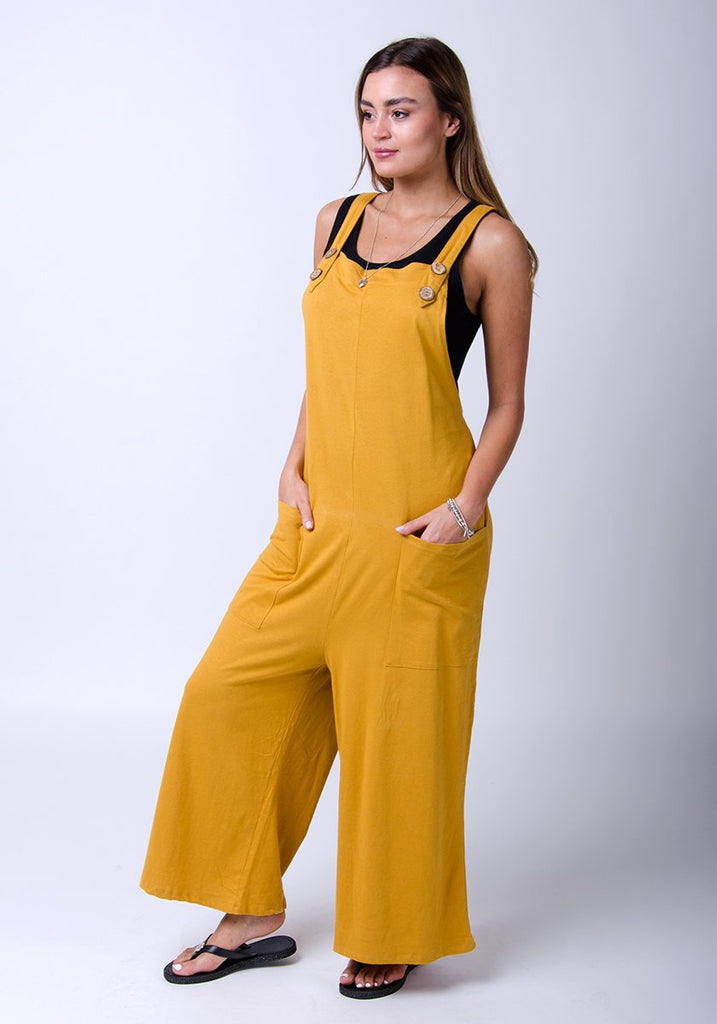 Amber-style, gold cotton jersey, wide-leg dungarees. Side-view, full-length pose highlighting functional pockets.