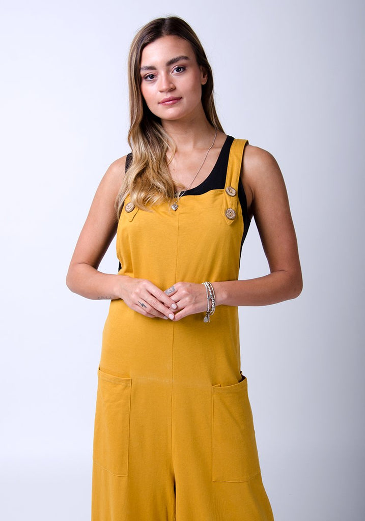 Frontal half-length pose wearing WASH brand, gold, cotton jersey dungarees.
