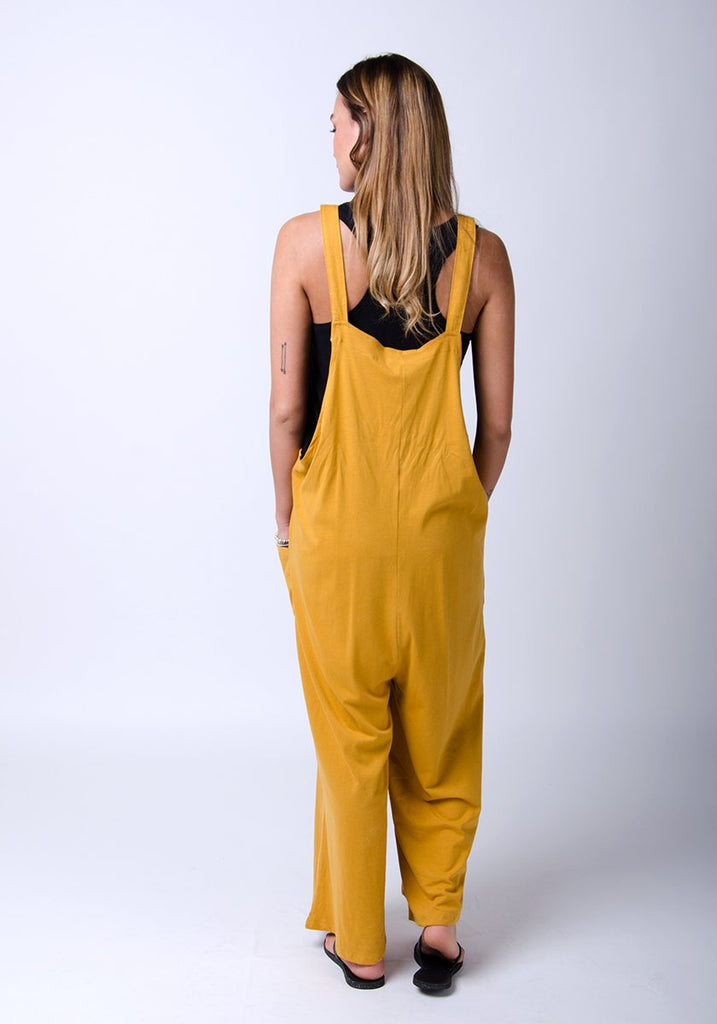 Full-length rear pose with Amber-style, gold, cotton jersey, relaxed-fit dungarees showing adjustable straps.