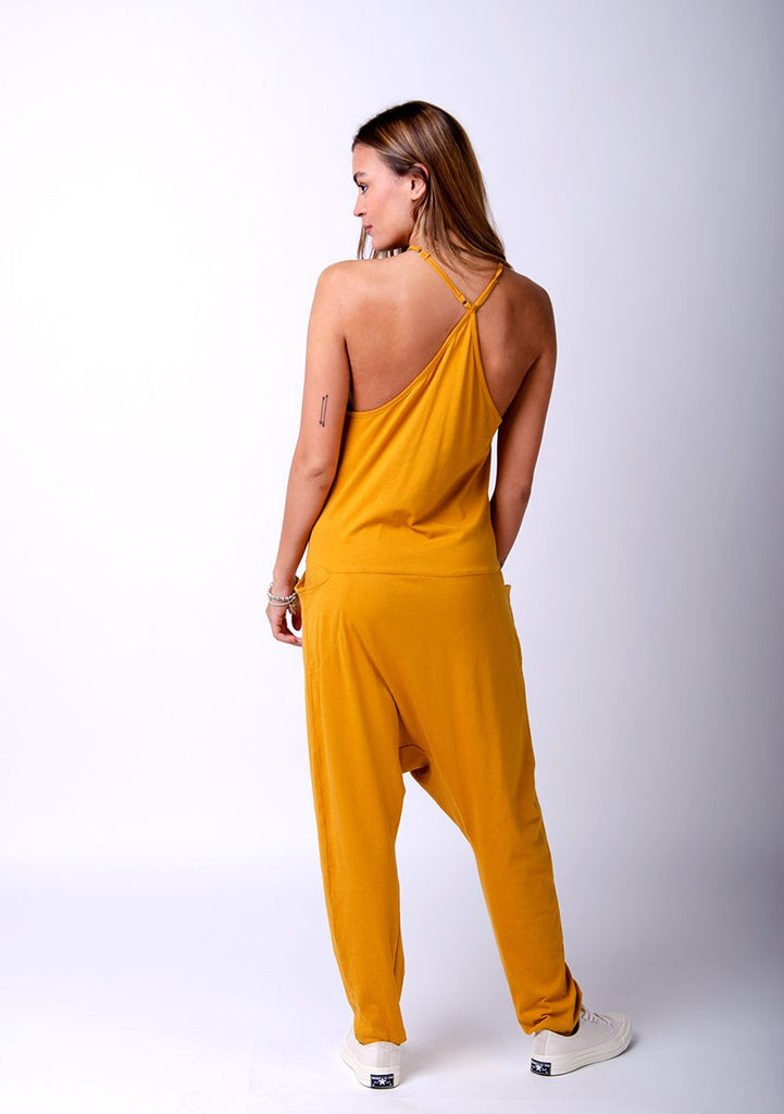 Full rear pose twisting to her left with hand in front pocket. Wearing Jools-style gold jersey jumpsuit showing crossed back straps.