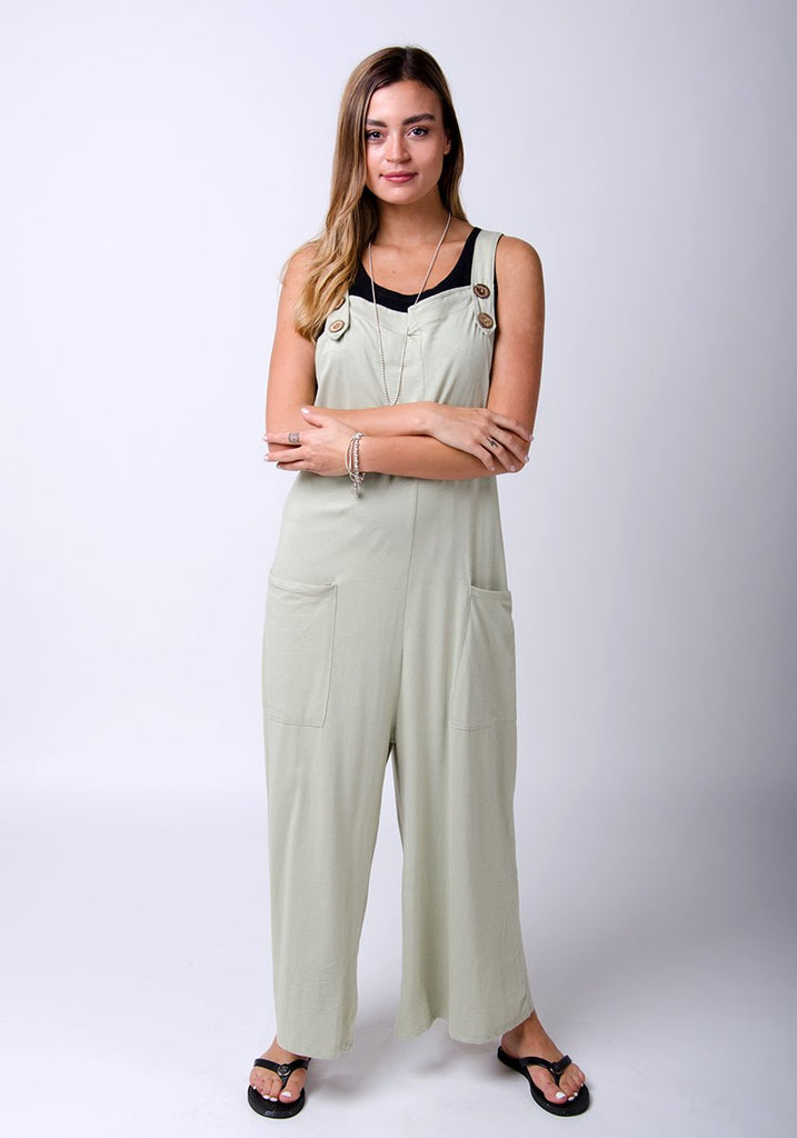 Full-length pose with folded arms wearing Amber-style, pale-green, cotton jersey, relaxed-fit dungarees.