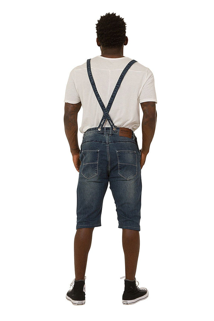 Full back pose showing rear pockets and adjustable straps of blue dungaree shorts.