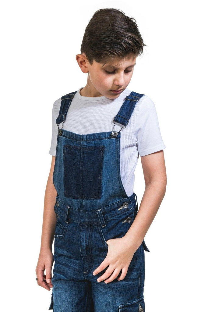 Diagonal front view of kids' denim dungarees with side button fastening and cargo pockets.