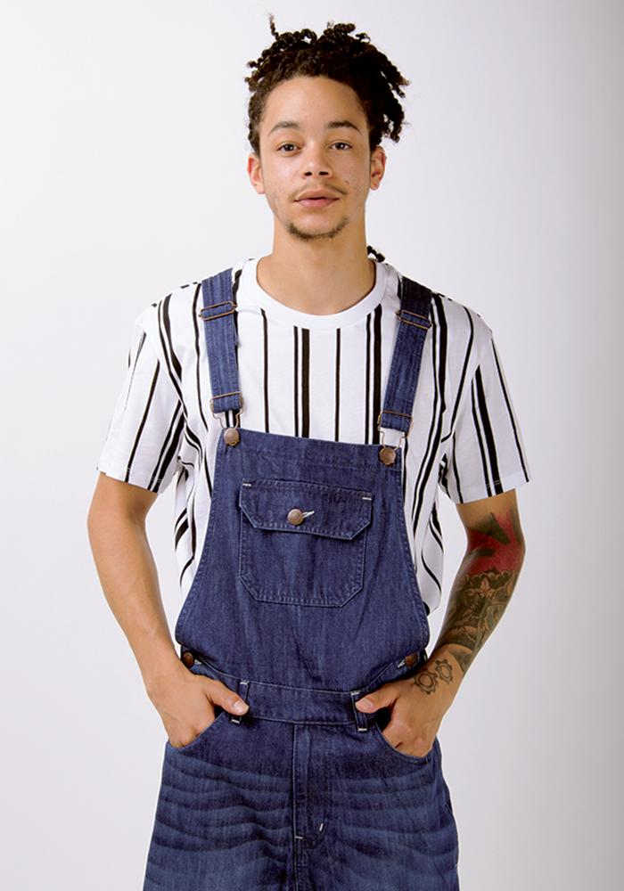 Focus on top-half of dark-wash bib-overall from Dungarees Online, with focus on adjustable straps with hands in front pockets.
