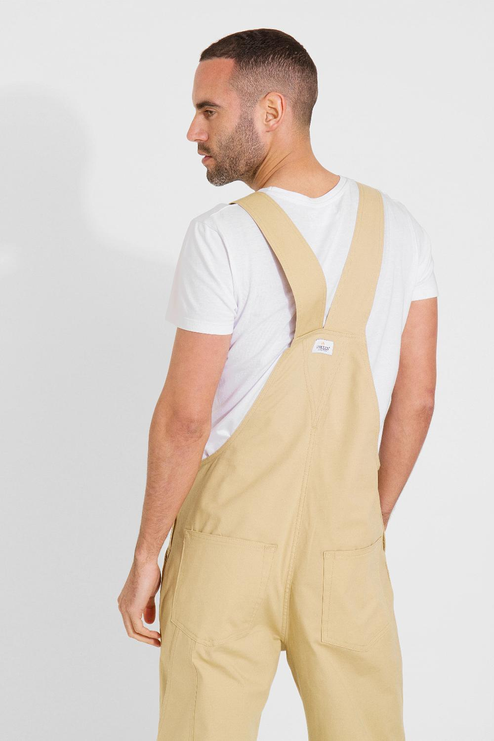 Looking to his left with back to camera focussing on top half of 'Christopher' brand dungaree shorts.
