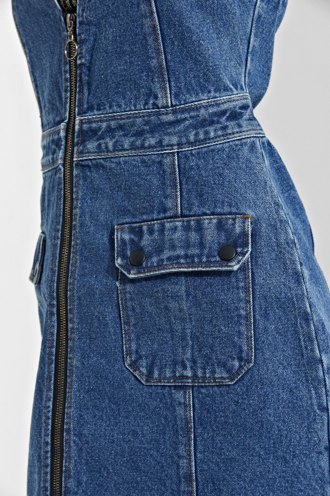 Mid-view of 'Lana' style mini jean dress in mid colour denim with clear view of front pockets and zip.