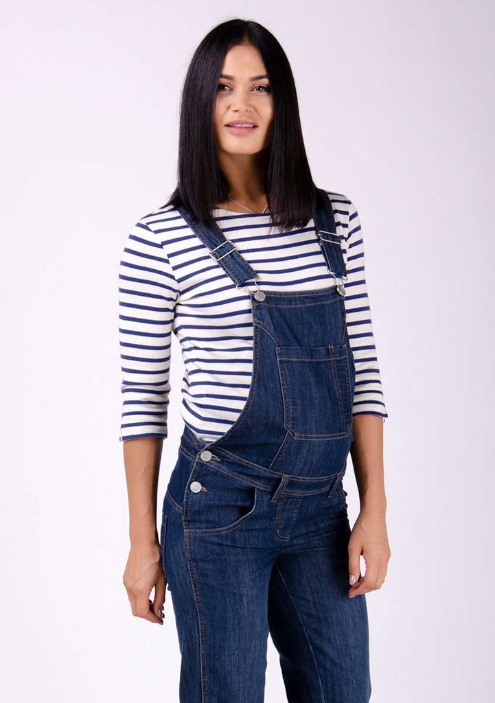 Two-thirds pose focussing on front pockets, side buttons and adjustable straps of dark wash maternity dungarees