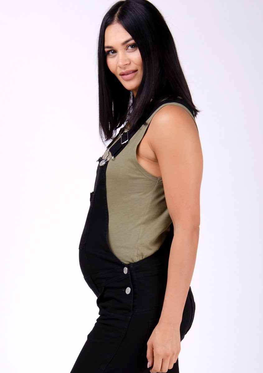 Half-side pose showing off bump wearing Dungarees Online's black dungarees.