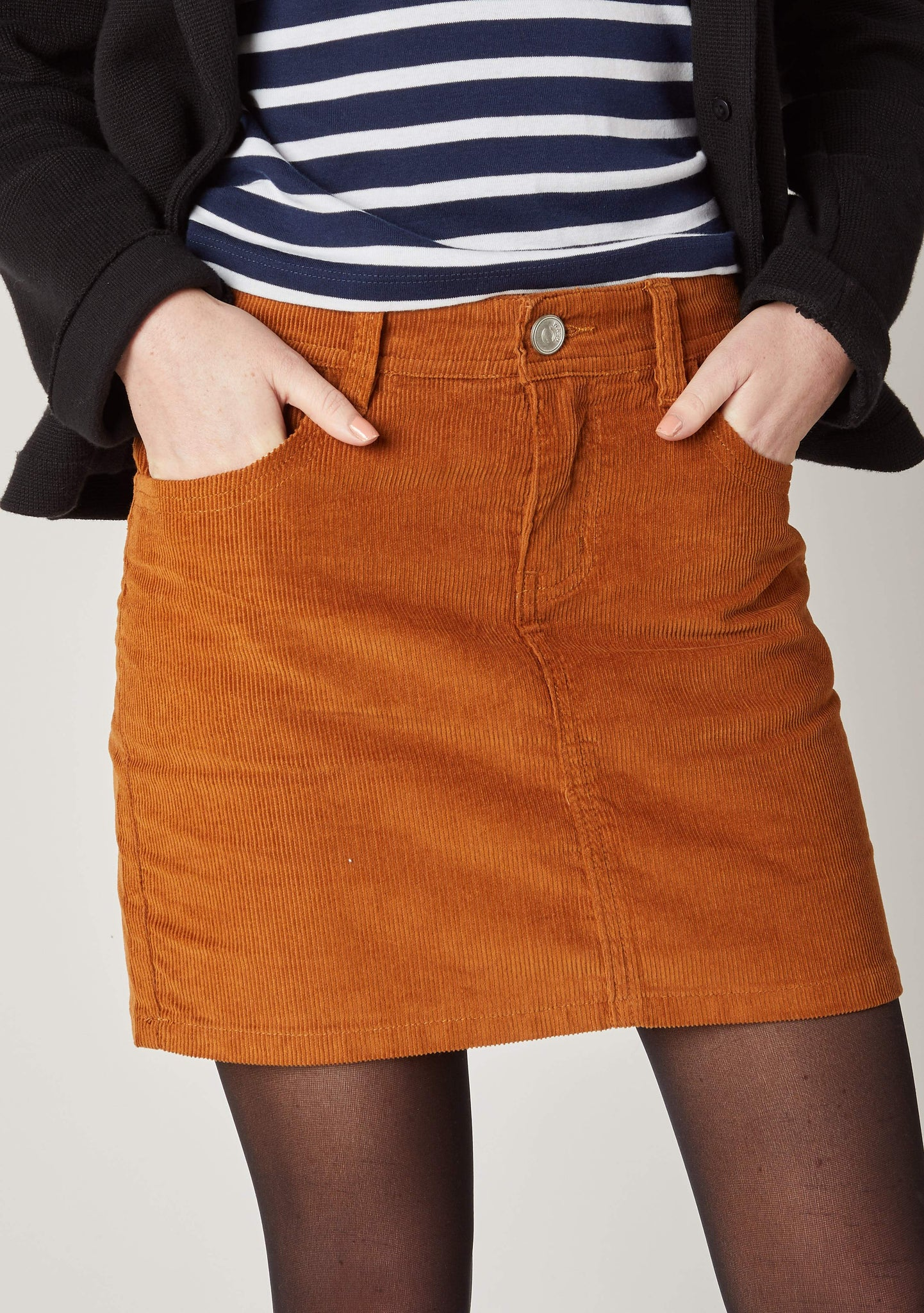 Close front view of brown corduroy skirt, with hands in front pockets with focus on belt loops, front zip and button fastening.