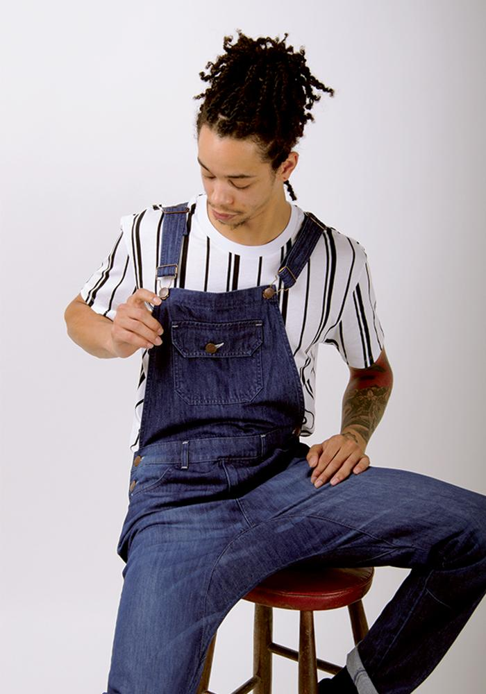 Sitting on stool, clasping right adjustable strap of 'Jesse' organic cotton, slim bib-overalls.
