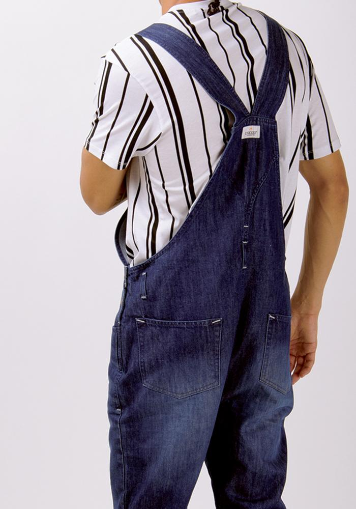 Rear view of dark wash bib-overalls from Dungarees Online, with focus on label, back pockets and cross back straps.