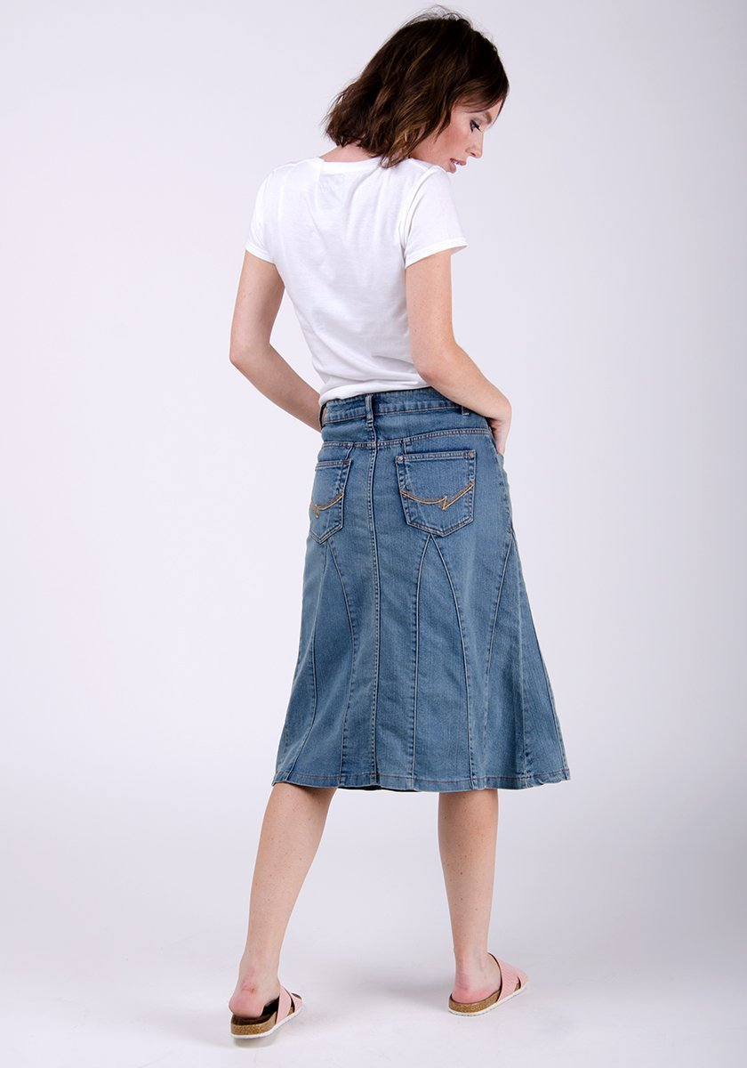 Full rear pose wearing soft panelled midwash denim skirt with back pockets.
