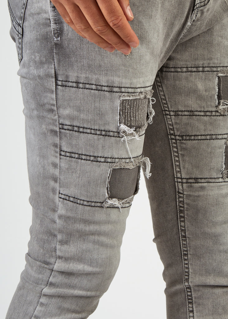 Close up view of the narrow fit leg on grey skinny fit dungarees with repaired patched detail