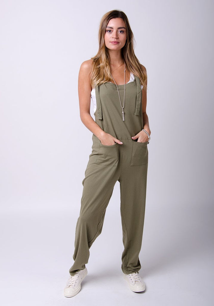Full frontal pose wearing practical Mabel-style jumpsuit with hands front pockets.