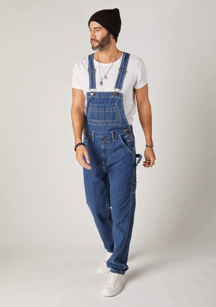Front pose looking to left wearing loose fitting, stonewash denim bib overalls with view of bib and front pockets and adjustable straps.