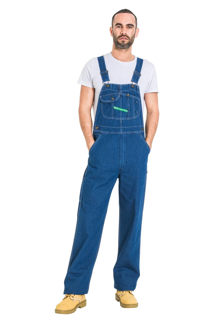 Full-length front view with hands in pockets, wearing 'Key Apparel USA' bib-overall made with premium materials and superior finish.