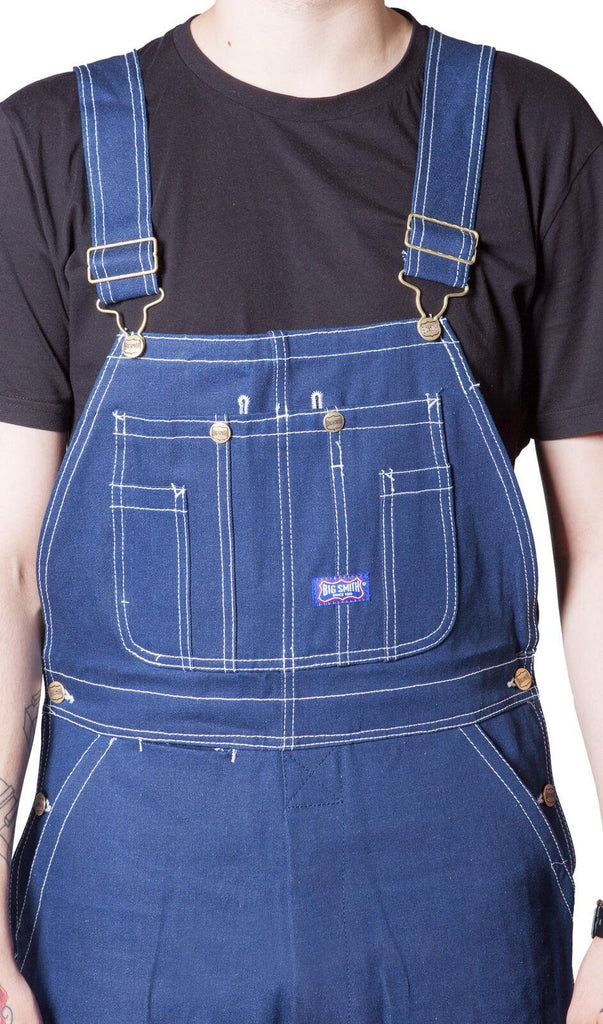 Showing bib details, triple stitched seams and utility pockets of work bib overalls.