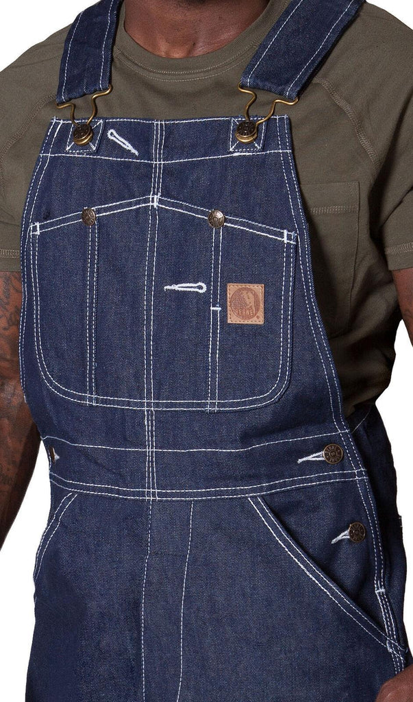 Showing bib details and utility pockets of American indigo work bib overalls.