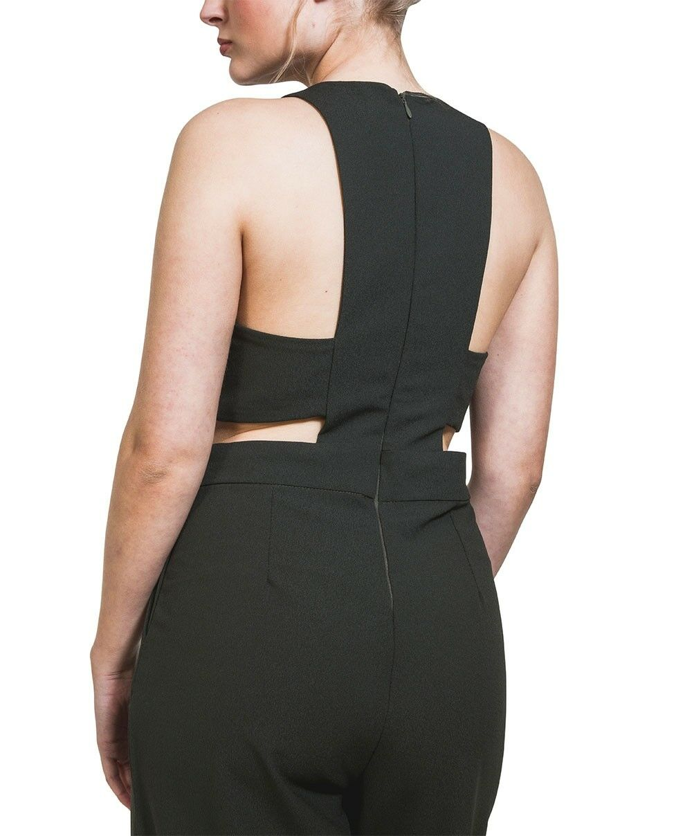 Rear midriff view of lightweight palazzo style jumpsuit with hands in front pockets and focus on back zipper.