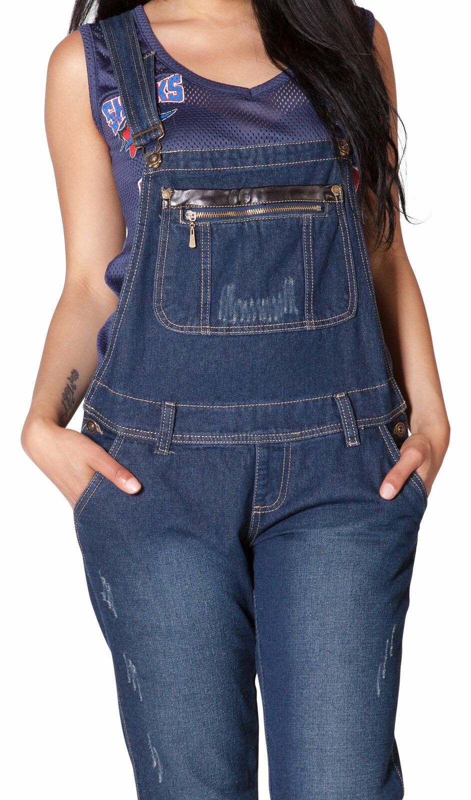 Frontal midriff view of dungarees with hands in front pockets and focus on adjustable straps, belt loops and bib pocket with zip and faux leather.